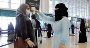 FILE PHOTO: A security woman checks the temperature of a woman at Riyadh International Airport, after Saudi Arabia reopened domestic flights, following the outbreak of the coronavirus disease (COVID-19), in Riyadh, Saudi Arabia May 31, 2020. REUTERS/Ahmed Yosri